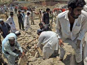 Des Pakistains cherchent des victimes sous les décombres.