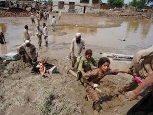 Des victimes des inondations au Pakistan tentent d'évacuer leur maison en périphérie de Peshawar.