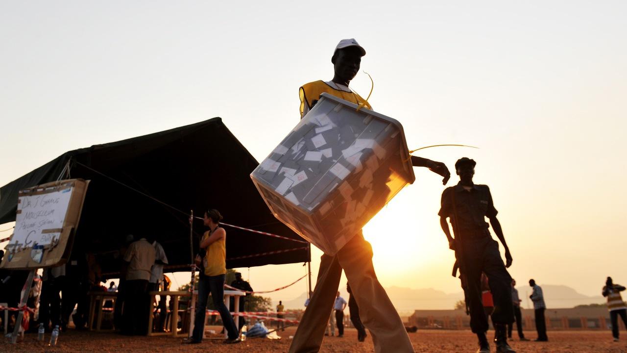 Un responsable du scrutin transporte une boîte de votes à la fermeture des bureaux, le 15 janvier 2011.
