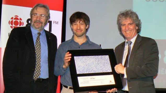 L'animateur des Années lumière, Yanick Villedieu, le récipiendaire, Joël Bêty et le directeur de l'information à Radio-Canada, Alain Saulnier