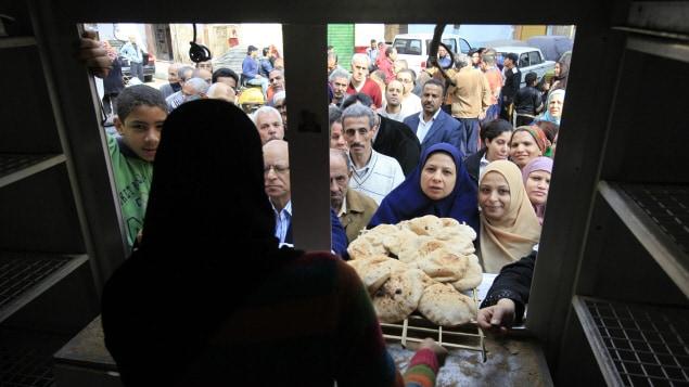 Des Égyptiens se pressent pour mettre la main sur du pain avant que le couvre-feu n'entre en vigueur.