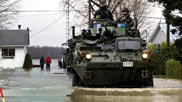 Un véhicule de l'armée circule dans une rue inondée de Saint-Jean-sur-Richelieu.