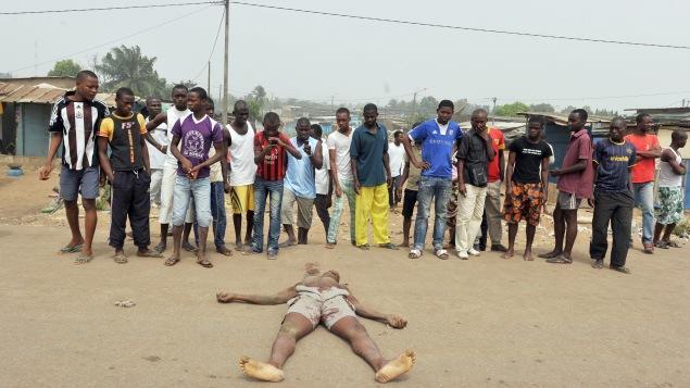 Des résidents observent le cadavre d'un homme tué par balle dans les rues d'Abidjan en janvier 2011.