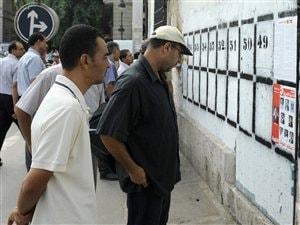 Des passants regardent des pancartes électorales à Tunis, le 1er octobre 2011.