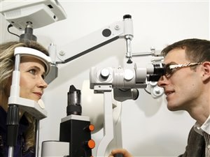 Un optometritste en train de réaliser une examen de la vue.