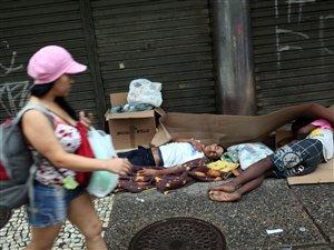 Une femme passe devant des sans-abri