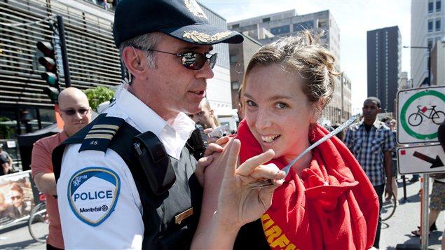 Un policier repousse une manifestante sur la rue Crescent, à Montréal, pendant le Grand Prix.