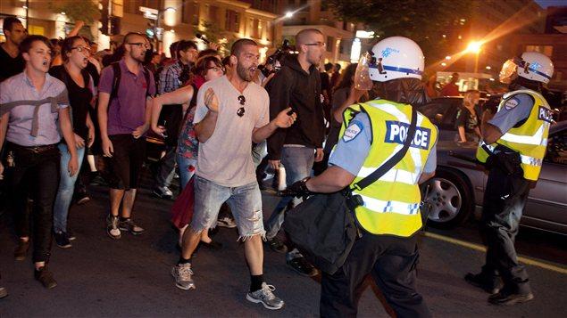 Les manifestants avancent vers les policiers près du site des festivités du Grand Prix, au centre-ville de Montréal, samedi soir.