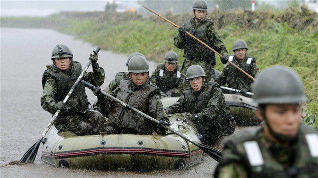 Militaires des forces d'autodéfense à la recherche de victimes des inondations