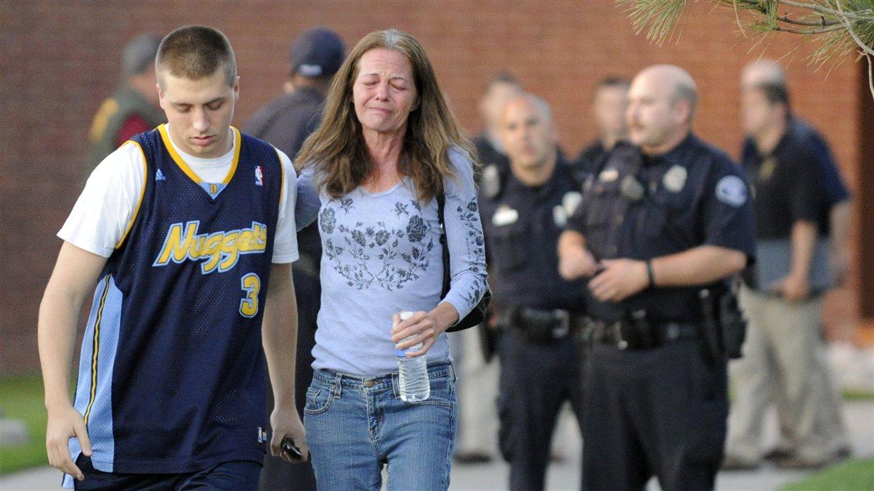 Jacob Stevens, 18 ans, témoin de la fusillade, et sa mère, Tammi, se réconfortent, après avoir été interrogés par les policiers, à Aurora.