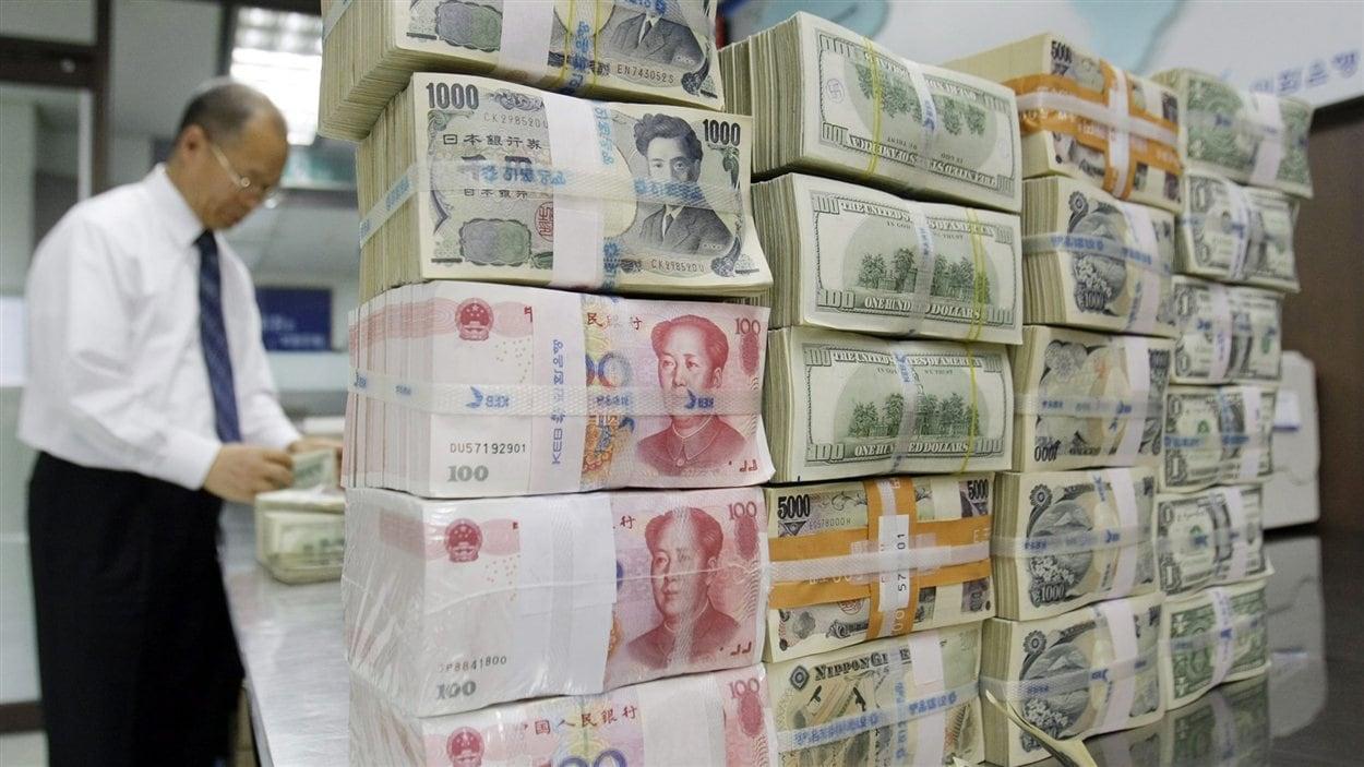Un employé d'une banque en Corée du Sud près d'une pile de billets en devises étrangères (archives).