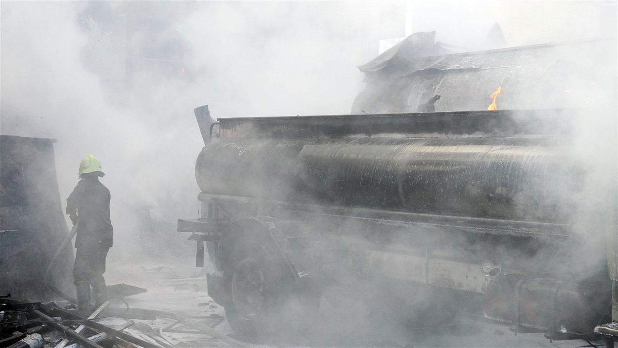 Des pompiers tentent de contrôler la situation après l'explosion d'une bombe à Damas, le 15 août 2012