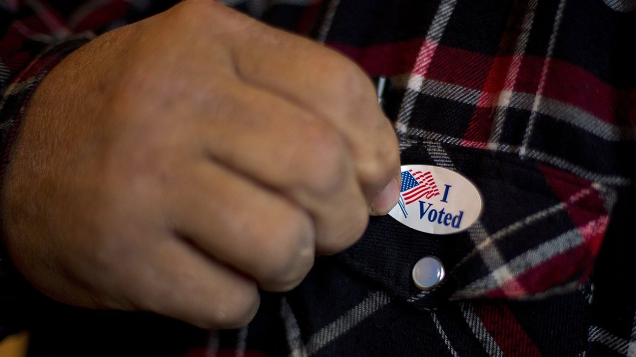 Un homme posant un autocollant « I Voted » sur sa chemise après avoir mis le bulletin dans l'urne à Otter Creek dans l'Iowa.