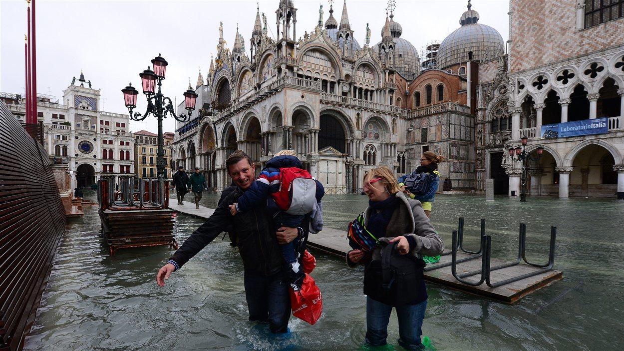 Des passants dans une rue inondée de Venise.
