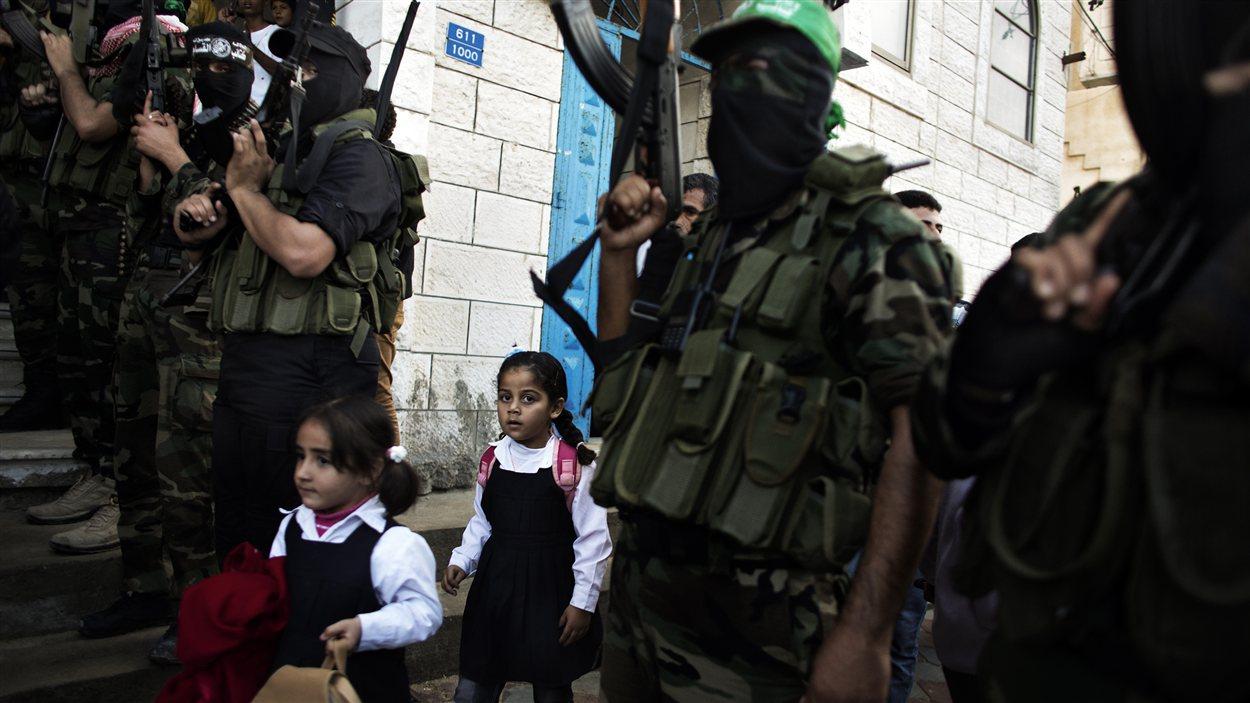 Des enfants palestiniennes dépassent des militants du Hamas armés réunis pour des funérailles à Gaza
