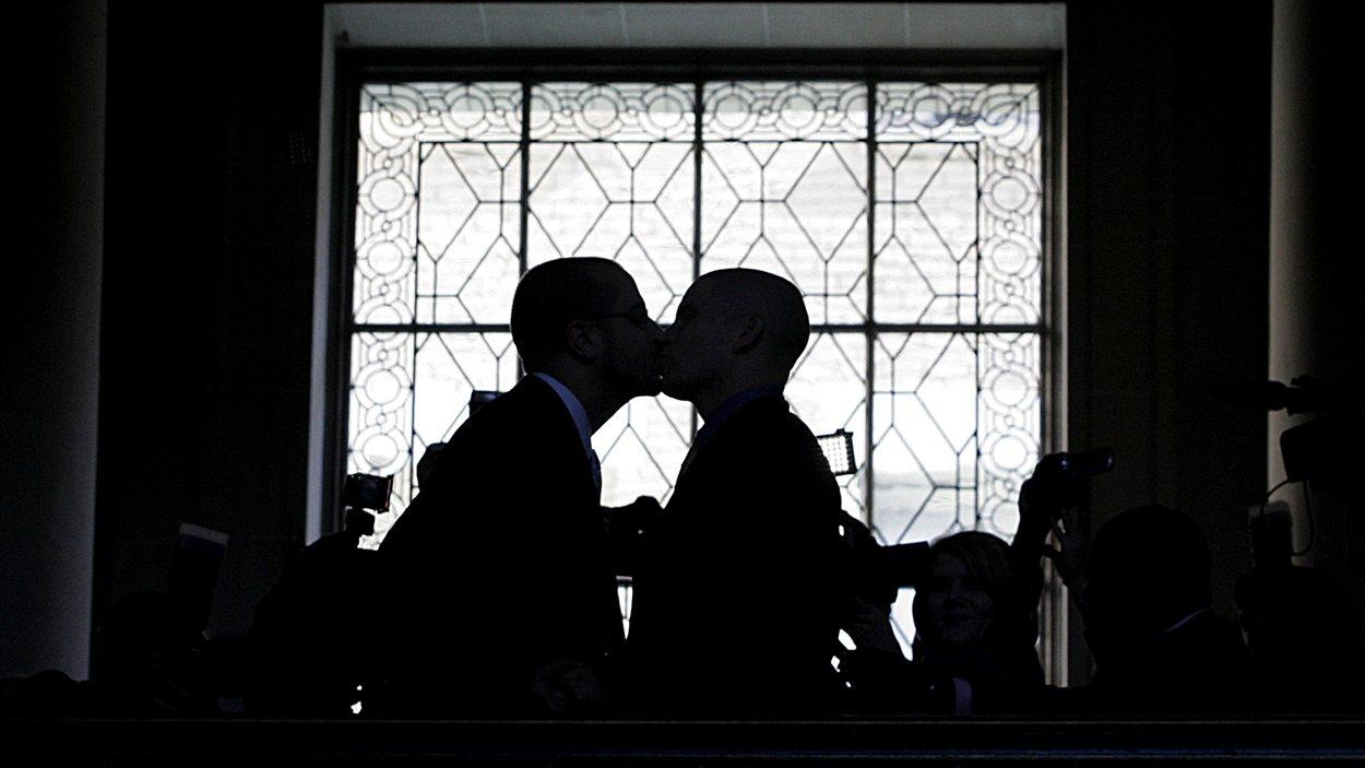 Un couple gai s'embrasse après avoir échangé es vœux à San Francisco.