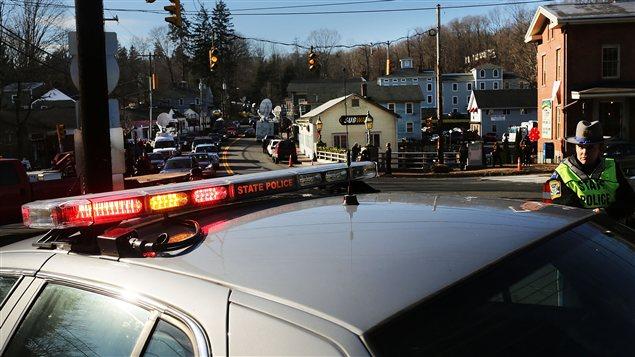 Des policiers montent la garde devant l'entrée de la rue qui mène à l'école Sandy Hook.