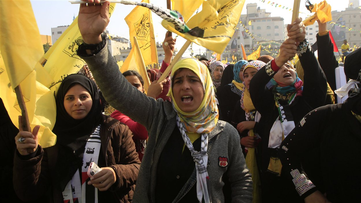 Des jeunes femmes agitent les drapeaux jaunes du Fatah lors d'une manifestation à Gaza pour fêter l'anniversaire du mouvement du président Mamoud Abbas, le 4 janvier 2013.