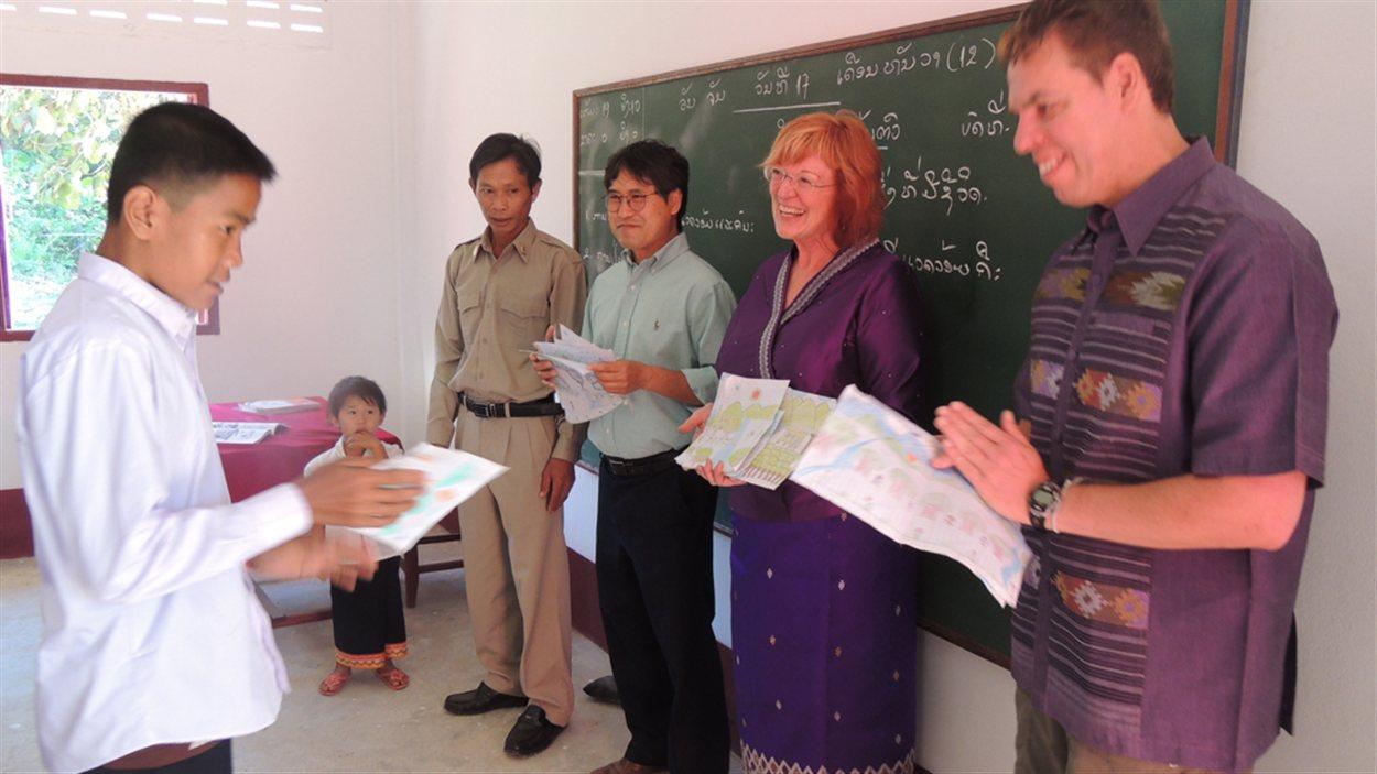 Un élève de cinquième année de l'école élémentaire de Ban Kava au Laos montre son dessin à François Tremblay (avant-plan gauche), Linda Lindsay et Ken Thongsay Phanlouvong, de School for Kids in Laos (SKL), le 17 décembre 2012.