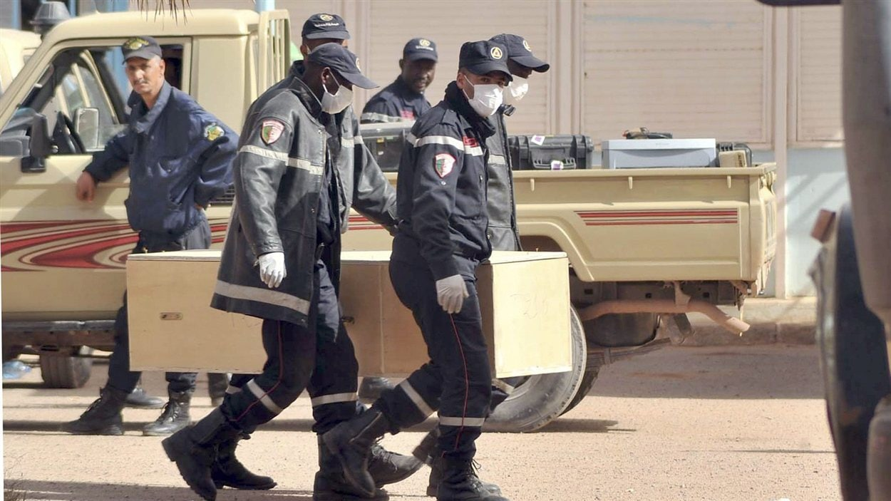 Des pompiers algériens portent un cercueil sur le complexe gazier d'In Amenas.