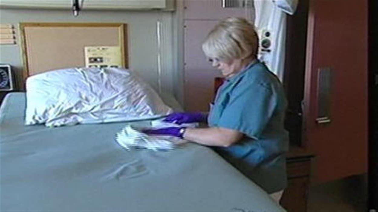 Une employée désinfecte un lit d'hôpital.