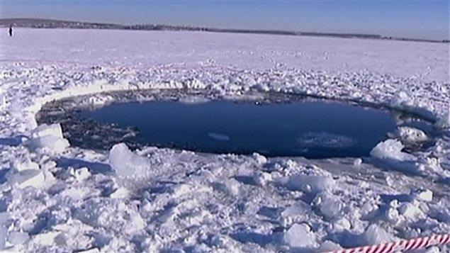 Le trou percé dans la glace d'un lac de l'Oural par un des débris de la météorite. L'objet a percé près d'une vingtaine de centimètres de glace.