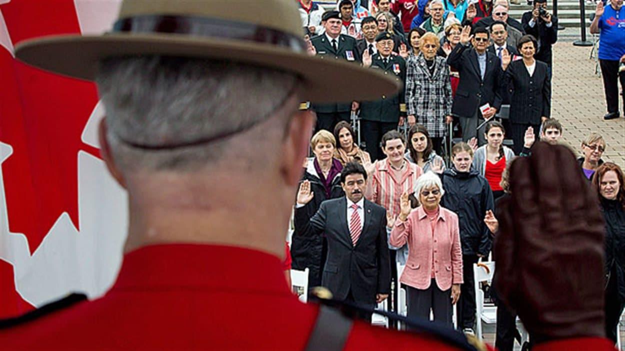 Un agent de la GRC lève la main devant un groupe de 60 immigrants venus prêter serment lors d'une cérémonie spéciale tenue l'an dernier à Vancouver pour le Jour du Canada.