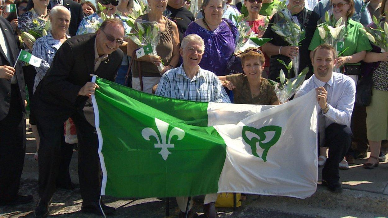 Le créateur du drapeau franco-ontarien, Gaétan Gervais (au centre), lors des célébrations de la Saint-Jean-Baptiste à Sudbury