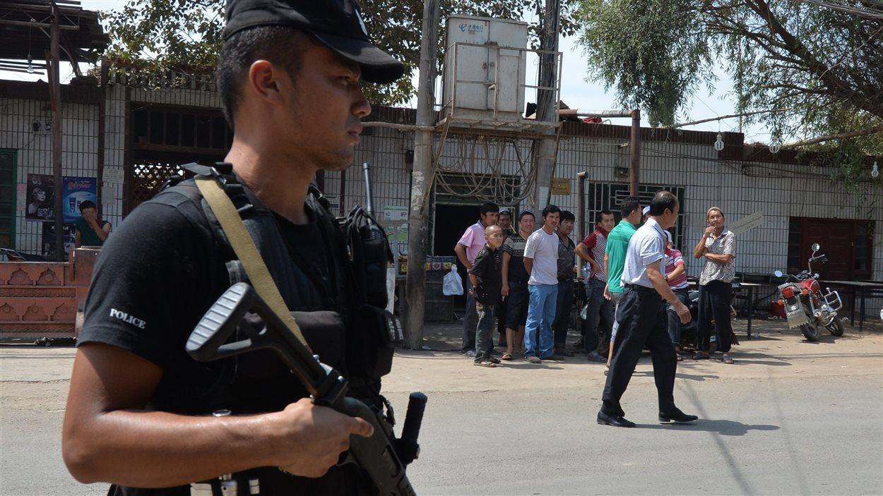 Un policier surveille la route empruntée mercredi par les émeutiers dans la ville de Lukqun, au Xinjiang.