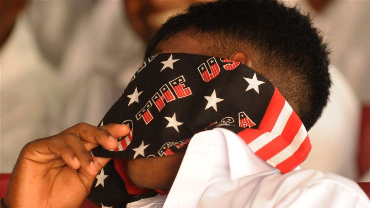 En 2011, un membre des Tigres tamouls se couvre le visage avec un foulard illustrant le drapeau américain.