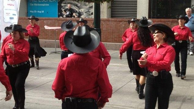 Des danseurs donnent un avant-goût du Stampede de Calgary au centre-ville le 4 juillet 2013.