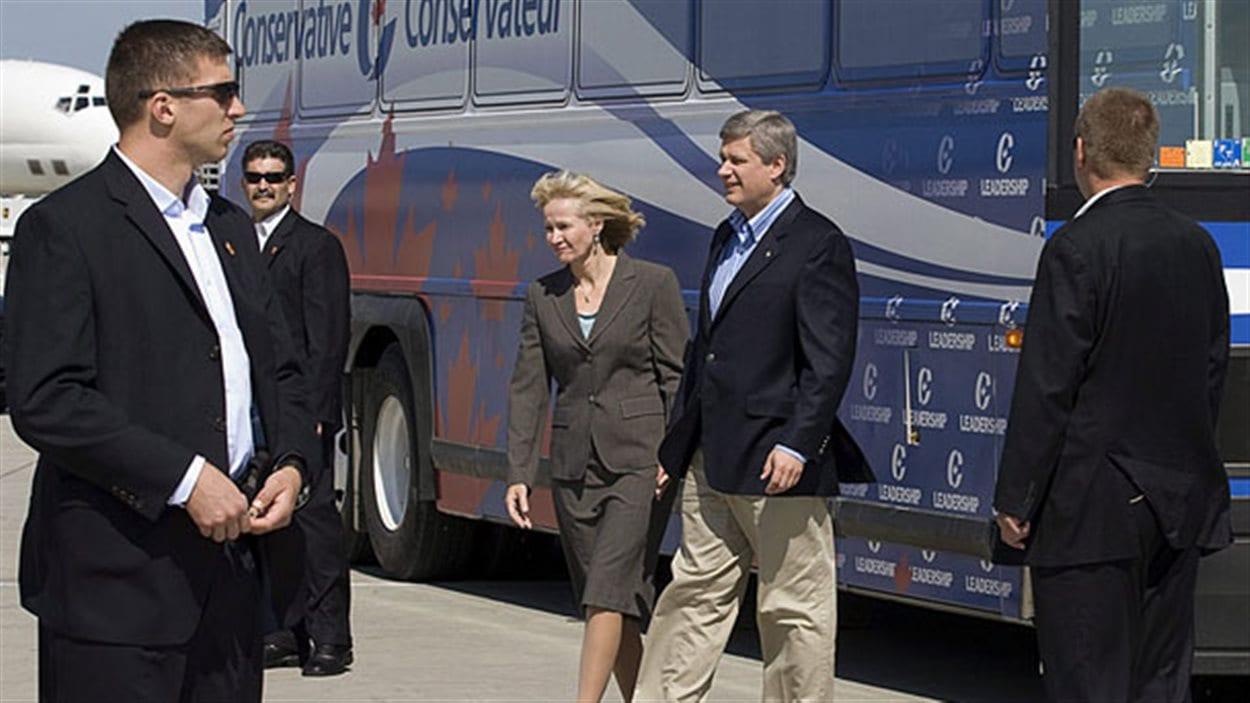 Le premier ministre Stephen Harper et sa femme protégés par des gardes du corps lors de la campagne électorale de 2008