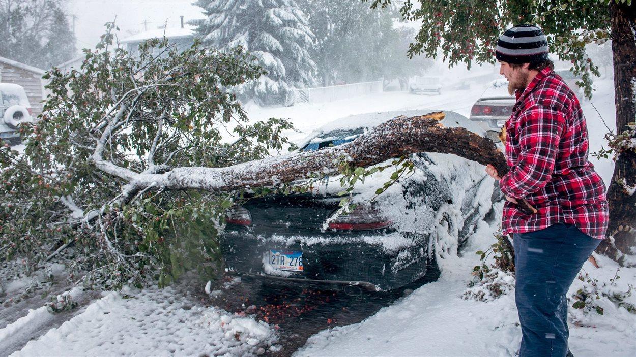 Un homme tente de nettoyer les dommages causés par une importante tempête hivernale, au Dakota du Sud