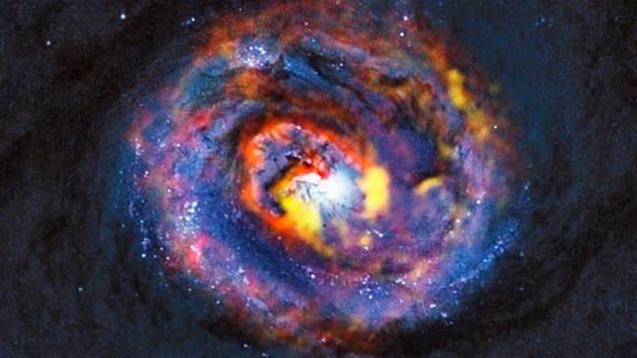 Cette vue détaillée montre les régions centrales de la galaxie active proche NGC 1433. L'image du fond, de couleur bleue sombre, a été obtenue par Hubble.  Elle montre l'existence de bandes de poussière au centre de la galaxie. Les structures colorées situées à proximité du centre apparaissent sur les observations d'ALMA qui ont révélé, pour la toute première fois, l'existence d'une forme spirale et d'un écoulement inattendu.