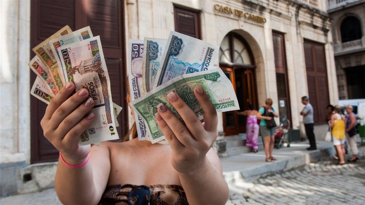 Une Cubaine présente des billets