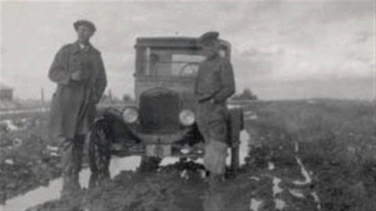 Deux passagers debout dans un champs près de leur voiture