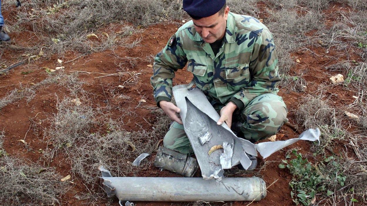 Un soldat libanais examine un des obus qui ont été tirés par l'armée israélienne dans le sud du Liban le 29 décembre 2013, sans causer de dommages.