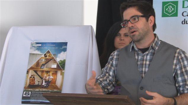 Jimmy Doucet, concepteur de la maison coupée en deux dont on peut apercevoir l'image à sa droite