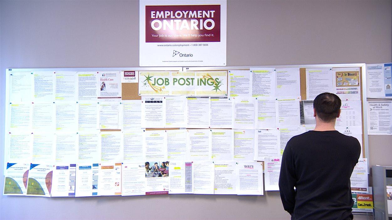 Un chômeur examine des offres d'emploi sur un babillard, à London, en Ontario.
