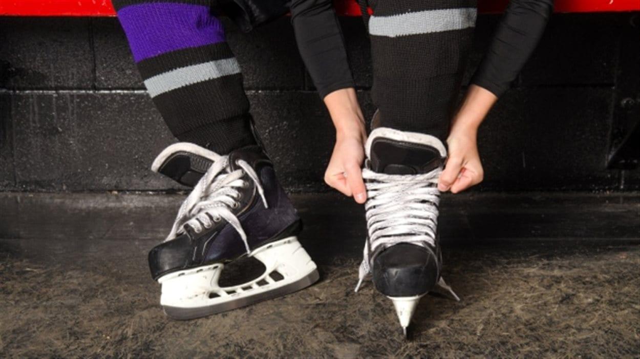 Un enfant attache ses patins de hockey