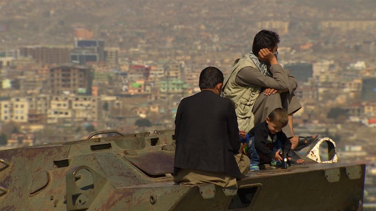 Des Afghans prennent une pause sur un vieux char d'assaut russe abandonné.