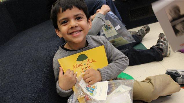 Un enfant recevant un livre neuf grâce au programme La lecture en cadeau de la Fondation pour l'alphabétisation.