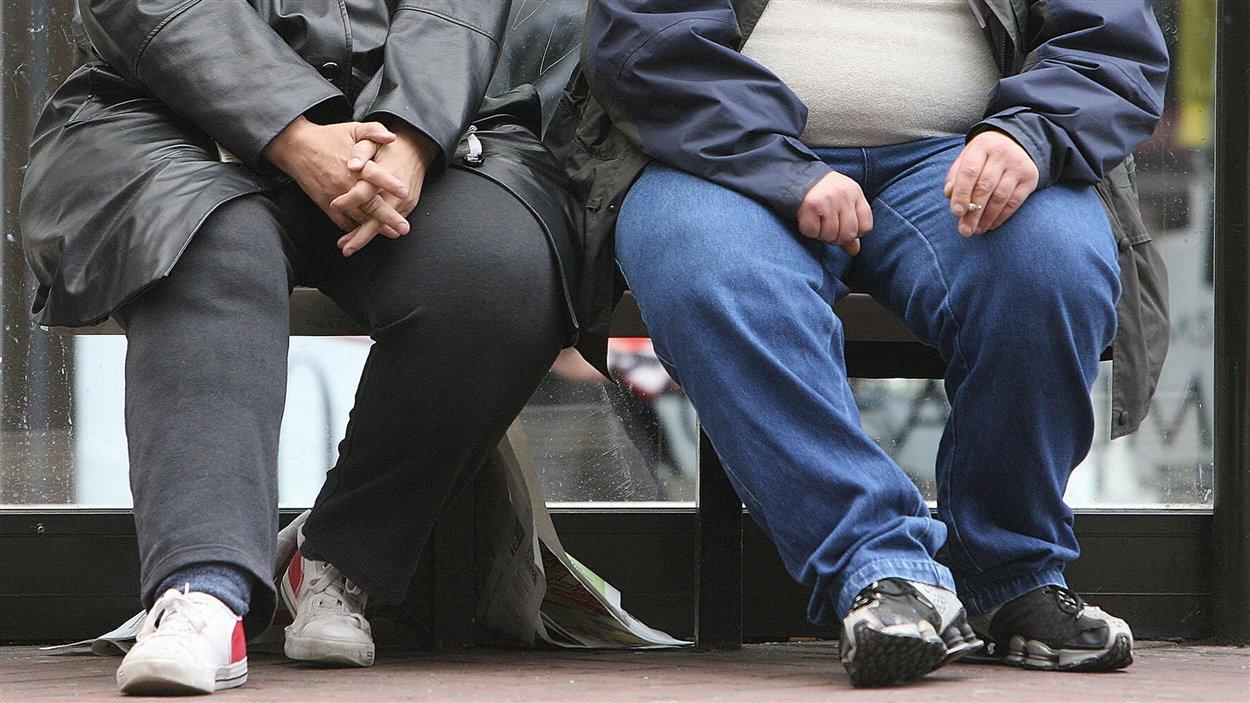 Un homme et une femme souffrant d'obésité attendent dans un abri d'autobus.