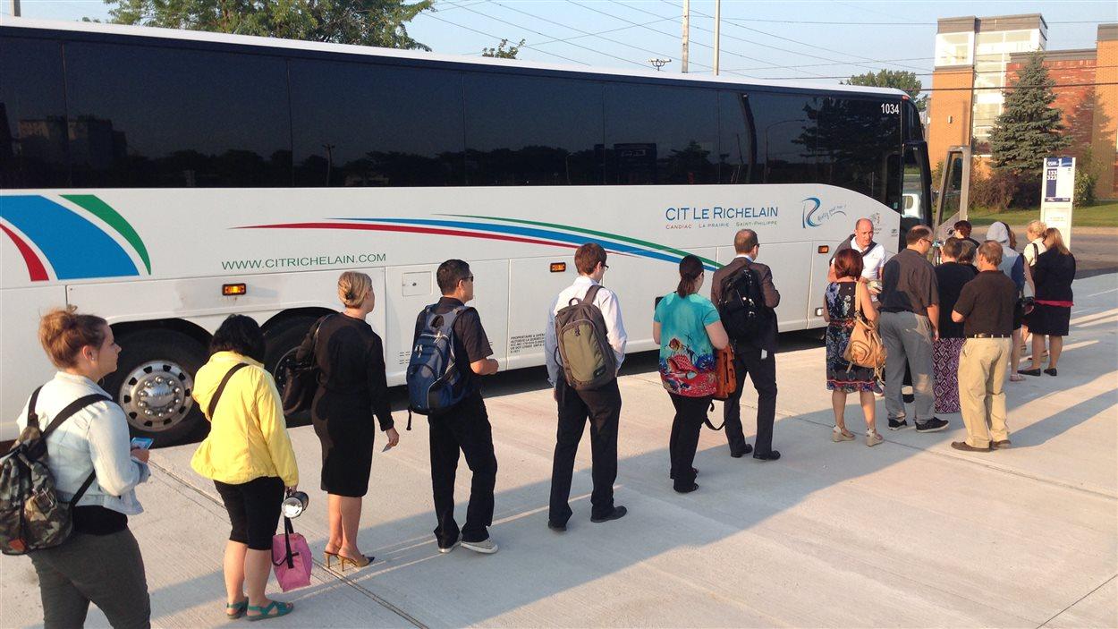 Des usagers embarquent dans un autobus au nouveau stationnement incitatif de Candiac