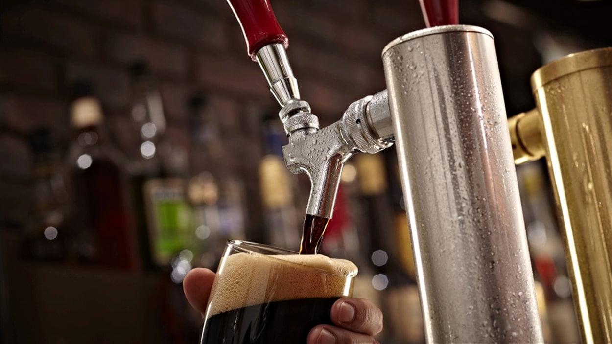 Un homme sert une bière pression.