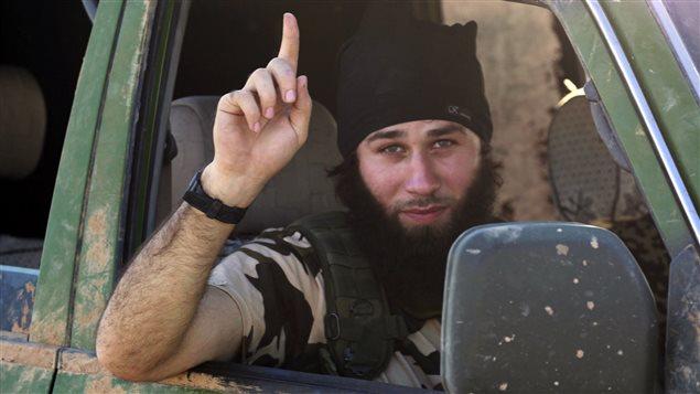 Un djihadiste de l'État islamique fait un geste de victoire dans une rue de Kobané.
