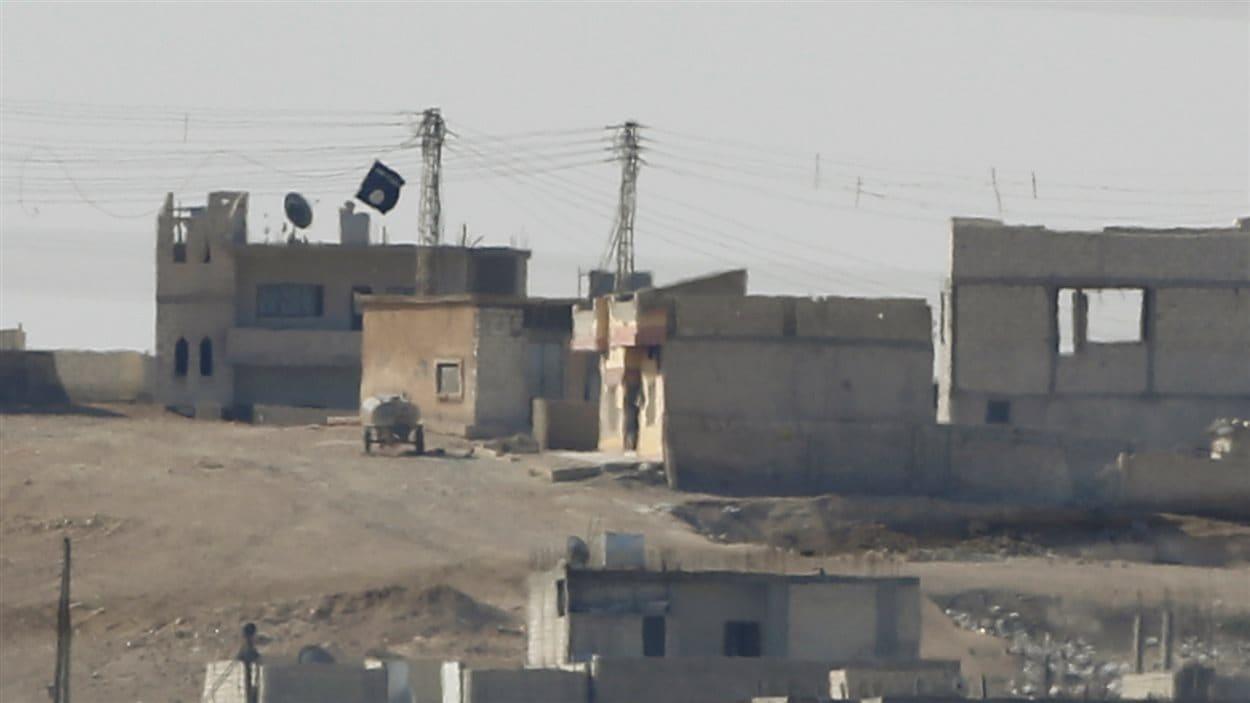 Un drapeau de l'État islamique flotte sur un bâtiment de Kobané.