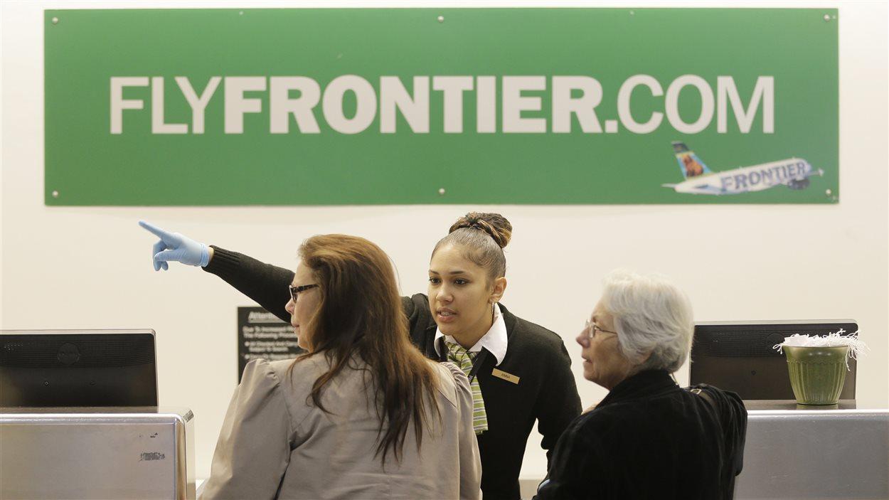 Une employée de Frontier Airlines à l'aéroport de Cleveland dirige des clients.