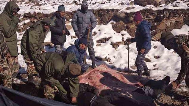 Des militaires népalais s'apprêtent à transporter des victimes.