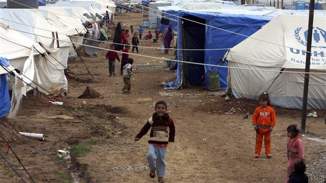 Des jeunes Irakiens réfugiés dans un camp après avoir fui les violences du groupe armé État islamique.